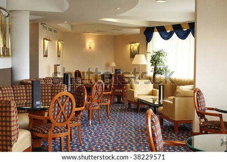 Hotel lobby. Chairs and tables in front of window - stock photo
