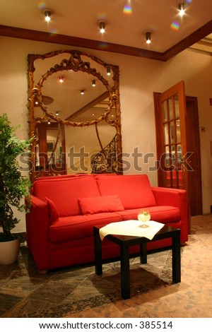 hotel lobby with red sofa and big framed mirror
