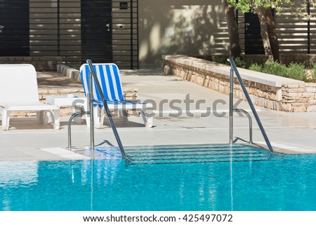 Hotel Poolside Chairs near a swimming pool. Summer shot