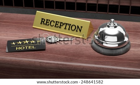 Hotel reception bell and and key on reception wooden desk - stock photo