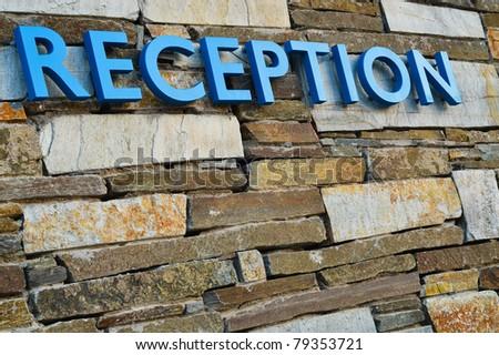 Hotel reception on random brickwork - stock photo