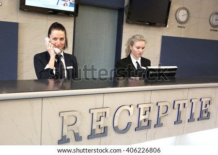 Hotel receptionist with phone. Modern luxury hotel reception counter desk with bell. Two happy females receptionist worker standing at hotel counter. - stock photo
