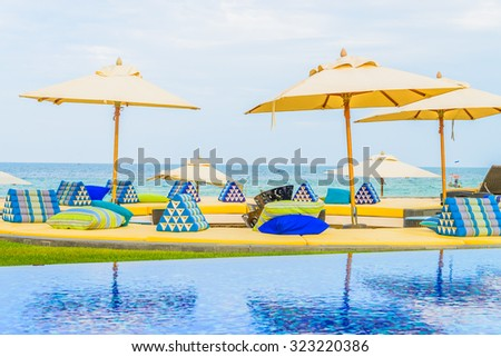 Hotel resort swimming pool with umbrella and chair on the beach