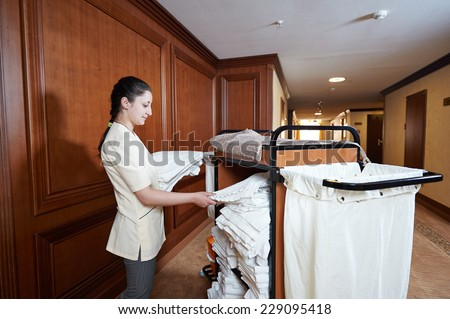 Hotel room service female housekeeping worker stock photo for Hotel room service cart