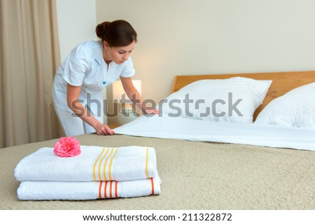 Hotel room service. Young maid changing bedclothes in a room - stock photo