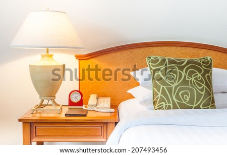 Hotel room setting with king sized bed, Thai silk green pillow, lamp, clock, telephone in hotel Thailand  - stock photo
