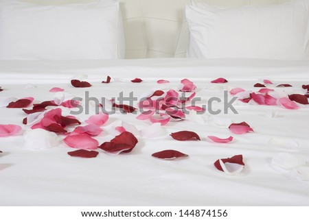 hotel room with big bed and red flowers - stock photo