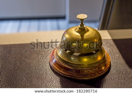 Hotel service bell on a reception counter - stock photo