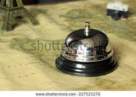 Hotel service bell on a world map in a vintage decorate with a camera and a monument on the background. Travel and accommodation concept. - stock photo
