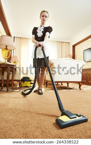 Hotel service. female housekeeping worker with vacuum cleaner in room apartment - stock photo