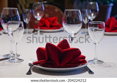 Hotel service: table in a restaurant with a white tablecloth, red napkins, wine glasses and cutlery.