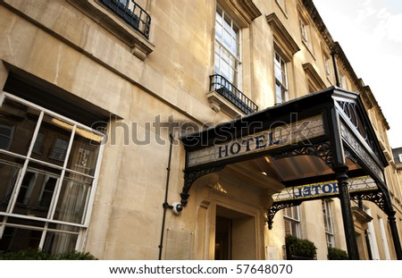 Hotel sign over the entrance to an old stone building - stock photo