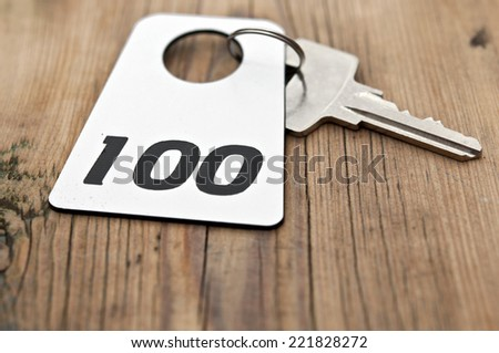 Hotel suite key with room number 100 on wood table  - stock photo