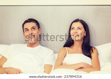 hotel, travel, relationships, and happiness concept - happy couple dreaming in bed - stock photo