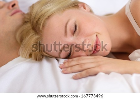 hotel, travel, relationships, and happiness concept - happy couple sleeping in bed - stock photo