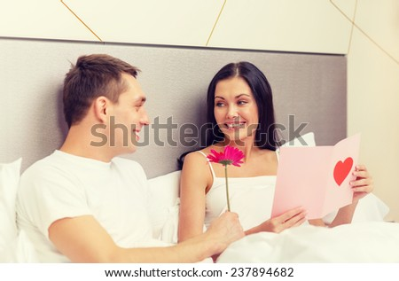 hotel, travel, relationships, holidays and happiness concept - smiling couple in bed with postcard and pink flower - stock photo