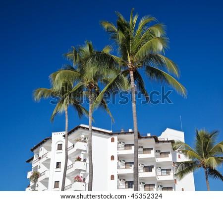 Hotel Tropicana with palm trees against bright blue sky, Puerto Vallarta, Mexico - stock photo