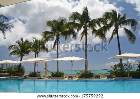 Hotel with swimming pool and palm trees - stock photo