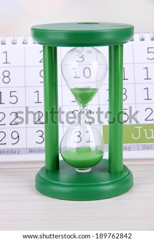 Hourglass and calendar on bright background - stock photo