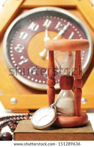 Hourglass and clock. Still-life with vintage retro watches - stock photo