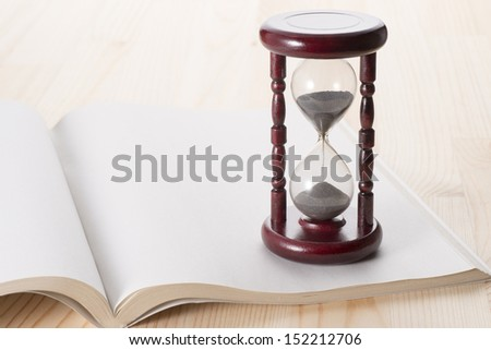 hourglass and open book on wooden table