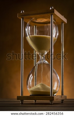 Hourglass close up with shad running through it on a rustic wooden table  - stock photo