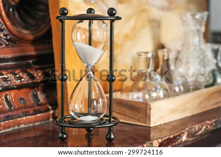 Hourglass counting down the time with sand running through the glass bulbs, - stock photo