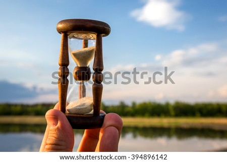 hourglass in hand against sky background - stock photo