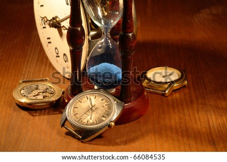 Hourglass, old watch and clock mechanism on wooden background - stock photo