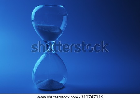 Hourglass on color background - stock photo