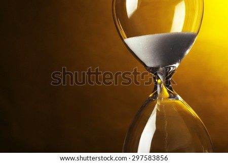 Hourglass on dark yellow background - stock photo