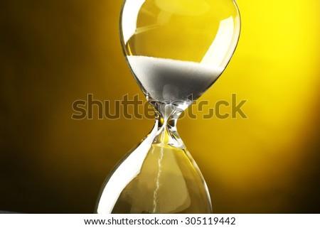 Hourglass on dark yellow background - stock photo