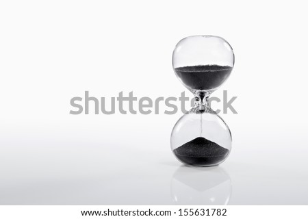 Hourglass on gradient white background with Black Sand. - stock photo