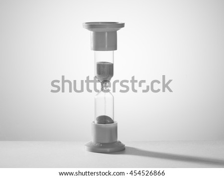 hourglass on gray bright light background with shadow