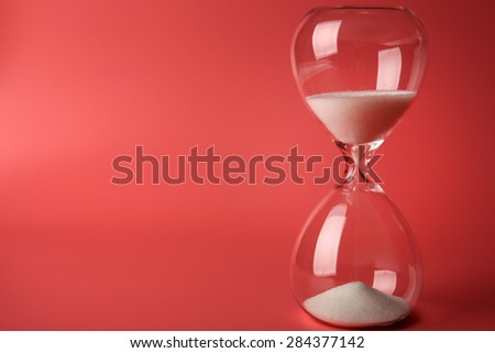 Hourglass on pink background - stock photo