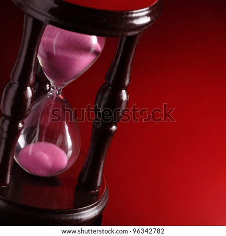 hourglass on red background - stock photo