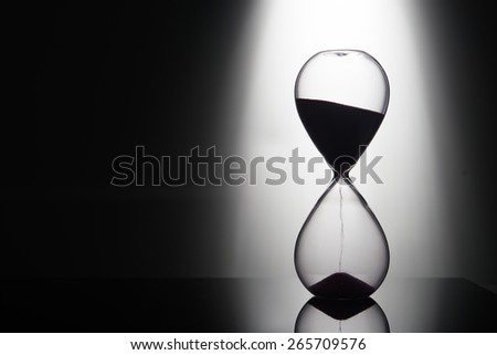 hourglass on the background of the light beam from behind - stock photo