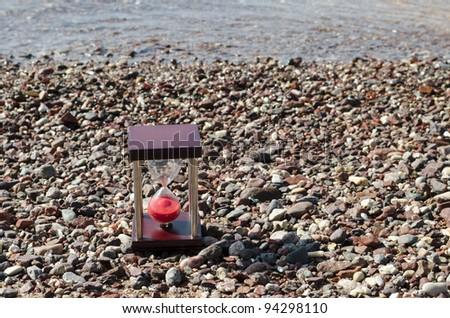 Hourglass on the beach - stock photo