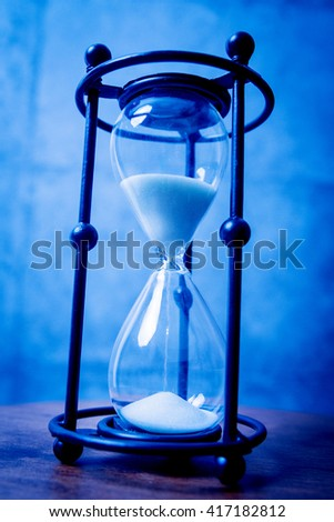 Hourglass on the wooden table. Background