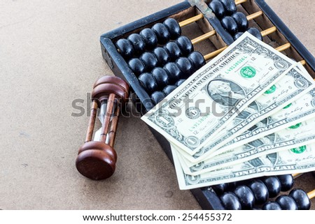 Hourglass with abacus and banknote - stock photo