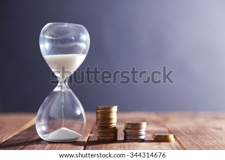 Hourglass with coins on wooden table on gray background - stock photo