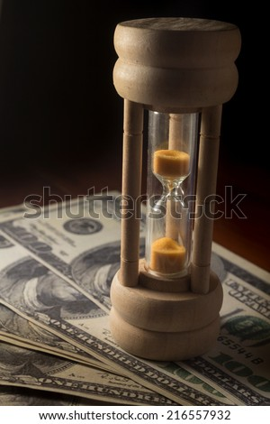 Hourglass with money,time and business concept. - stock photo