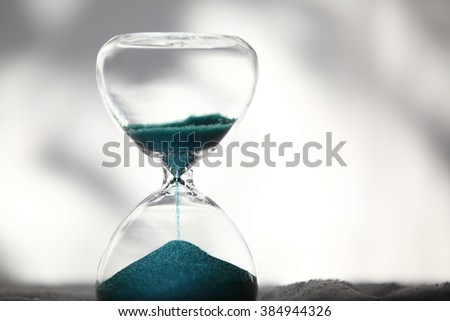 hourglass with shining light on bright background - stock photo
