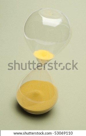 Hourglass with the sand almost all the way on the bottom to symbolize time running out. - stock photo