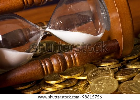 Hourglasses and coin On a wooden table - stock photo