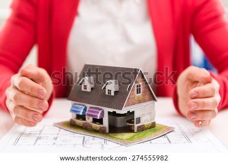 House agent offering new real estate to customer sitting at desk in the office. Shallow depth of field.  - stock photo