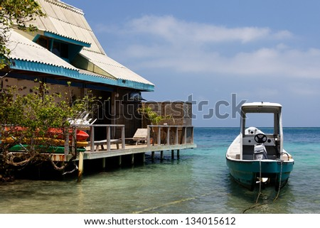 House and Boat in a Lagoon in the Caribbean Islas del Rosario near Cartagena de Indias, Colombia. - stock photo