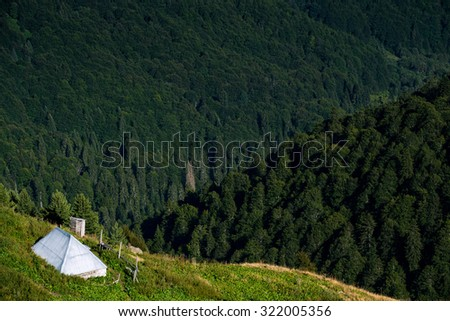 house and farm in wooded mountains of the Dinaric Alps in the summer, the wild places of our planet - stock photo