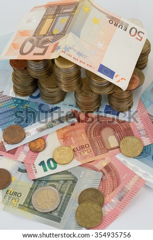 House and stack of euro coins and notes isolated