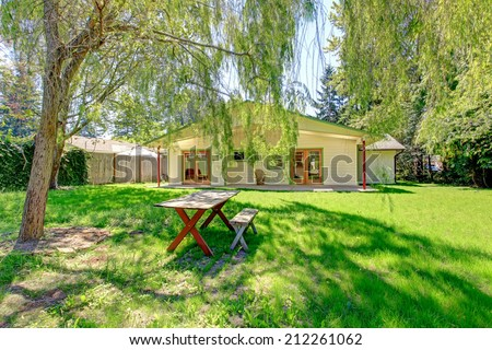 House backyard with green lawn and wooden table with benches - stock photo